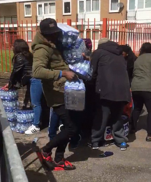 This is the shocking moment people armed with shopping trolleys stole trays of bottled water intended for London Marathon runners. Dozens of people swarmed around water stations at the side of the 26.2-mile route in Deptford, South East London, as they shamelessly began loading litres of Buxton water into their bags.
